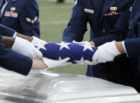 Gloved hands respectfully fold and handle the flag.  (U.S. Air Force photo by Senior Airman Willard E. Grande II)