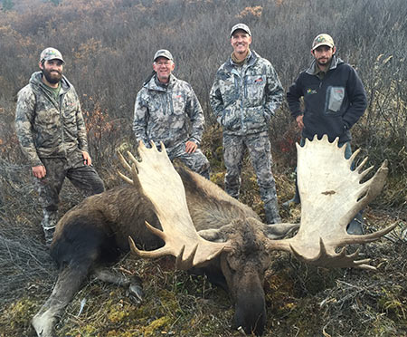 "This is a serious moose, 67"" wide, big palms and fronts — and lots of points; it will score way up in the record books. (l-r) Logan Young (guide), myself, Matt Fleming (the shooter) and Levi Letkeman (guide)."