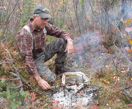 Larry Potterfield, Founder and CEO of MidwayUSA, cooking fresh moose meat